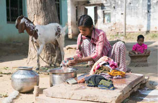 A woman washes clothes in rural India.