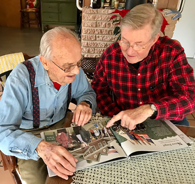Paul Dillon (right), illustrator of N is for Never Forget: POW-MIA A to Z (Elva Resa, 2017) points out a likeness of former POW Bill Koeln in one of his illustrations in the book.