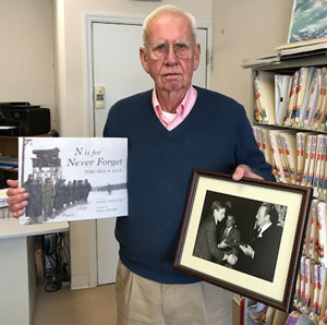 Skip Schumacher holds his copy of N is for Never Forget and a photo of himself receiving an award from actor John Wayne. Skip was on the USS Pueblo when it was seized by the North Koreans in 1968 and was held prisoner for 11 months.