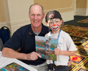 Tim Hoppey poses with a child of a fallen firefighter at the National Fallen Firefighters Foundation 2012 Memorial Weekend.