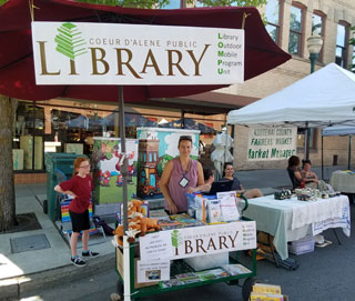 Barbara Brambila-Smith of the Coeur d'Alene Public Library talks with Farmer's Market visitors. Sales of Mudgy and Millie books, stuffed animals, and other related story items benefit the library foundation.