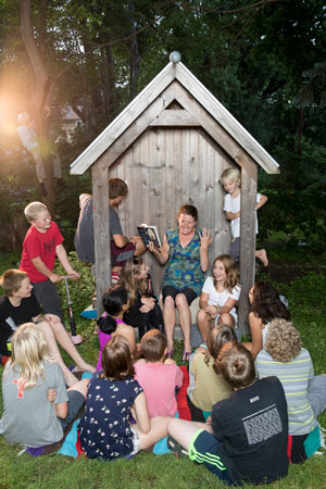 Kelly Barnhill reads her book <i>The Girl Who Drank the Moon</i> to neighborhood kids in her back yard. Photo by Ackerman+Gruber.