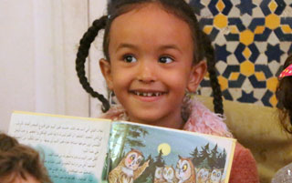 A girl reads a book at the Medina Children's Library in Fez, Morocco