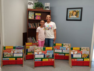 Sydney Dickerson and her mom, Tiffany, display colorful home libraries provided by Sydney's Book Club. The club worked with the Housing Authority of the City of Goldsboro, North Carolina, to provide children's books and book racks for families who needed them.