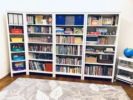 Colorful, accessible book bins allow children's books to be organized by topic and easily accessible for kids. Photo by Casey F.