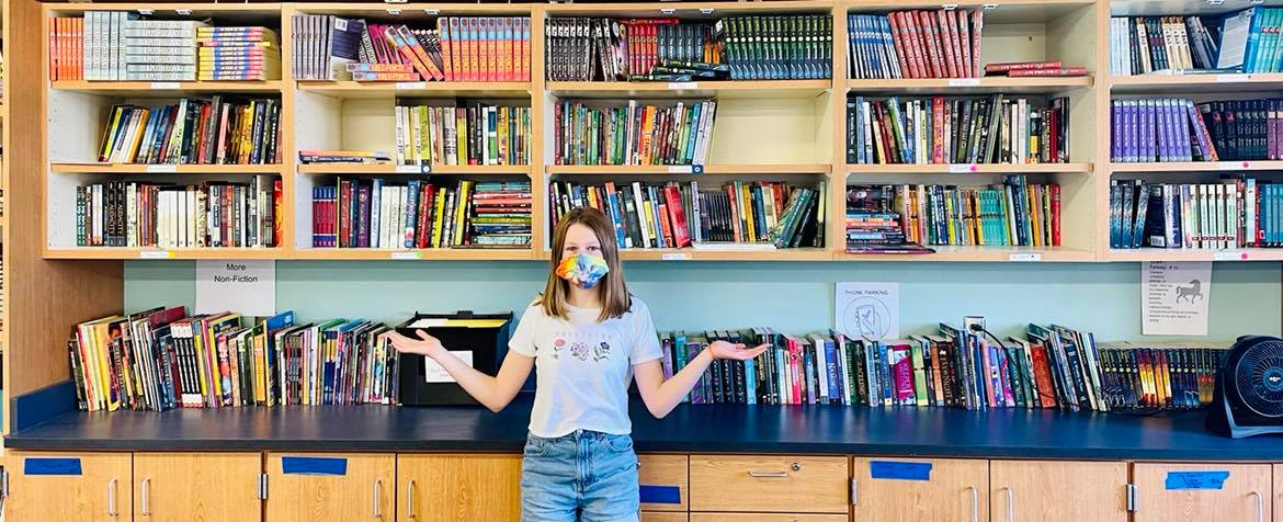 Student Maeve Putman gets ready to explore the library in Bridgette Haven's 8th grade Language Arts classroom. Shelves are filled with books that span numerous genres and interests. Students maintain the classroom library, labeling and sorting each book by common identifiers like genre and Lexile level.